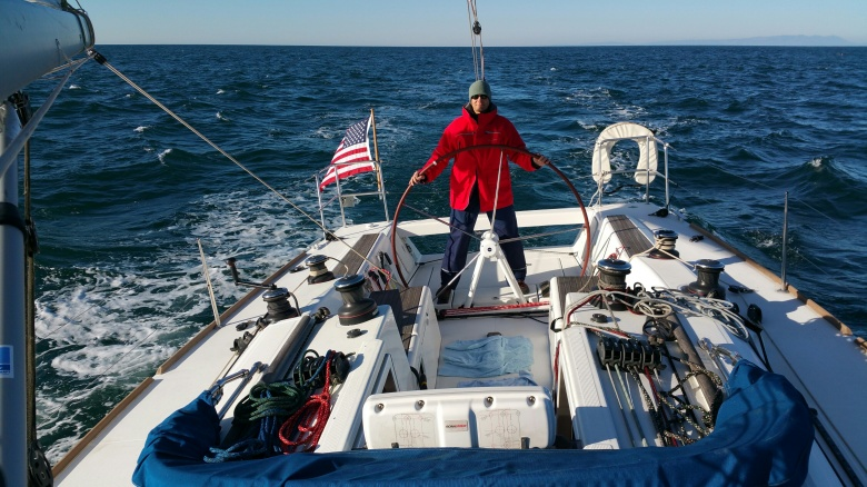 Mark Sanders staying warm on the helm on the helm, somewhere near Pt. Conception.